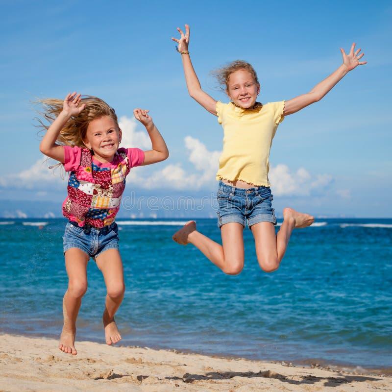 Dos hermanas que juegan en la playa fotos de archivo libres de regalías