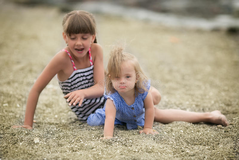 Dos hermanas que juegan en la playa foto de archivo