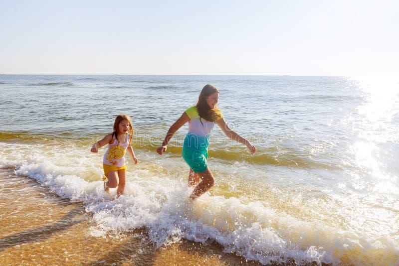 Dos hermanas que juegan en la playa en la puesta del sol fotografía de archivo