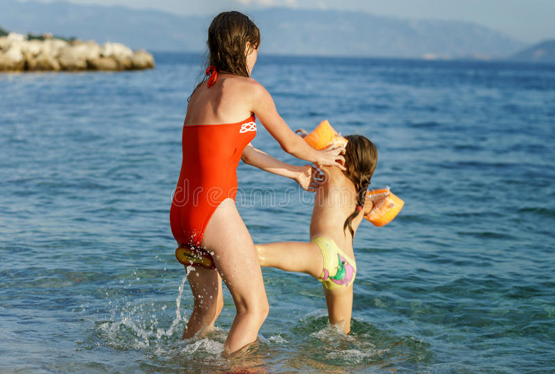 Dos hermanas que juegan a juegos y que nadan en el mar imágenes de archivo libres de regalías