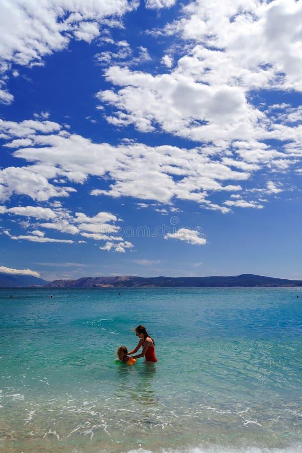 Dos hermanas que juegan a juegos y que nadan en el mar imagen de archivo libre de regalías