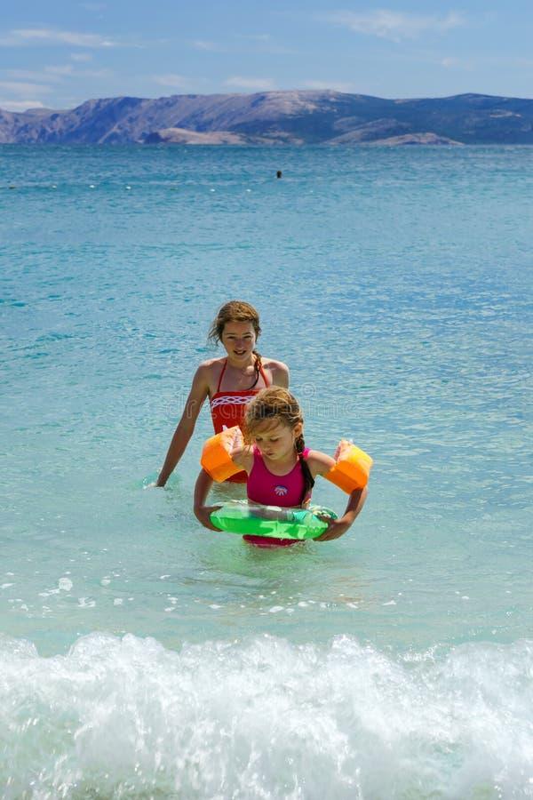 Dos hermanas que juegan a juegos y que nadan en el mar imagenes de archivo