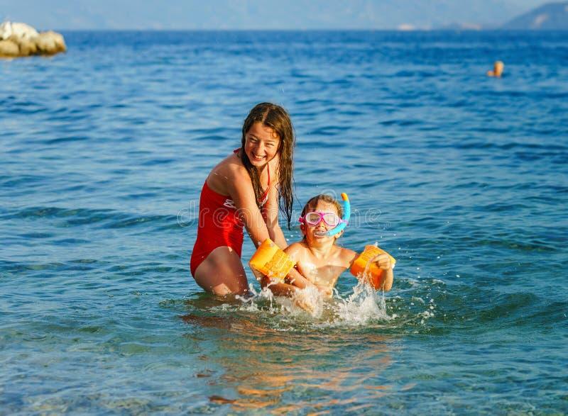 Dos hermanas que juegan a juegos y que nadan en el mar fotografía de archivo