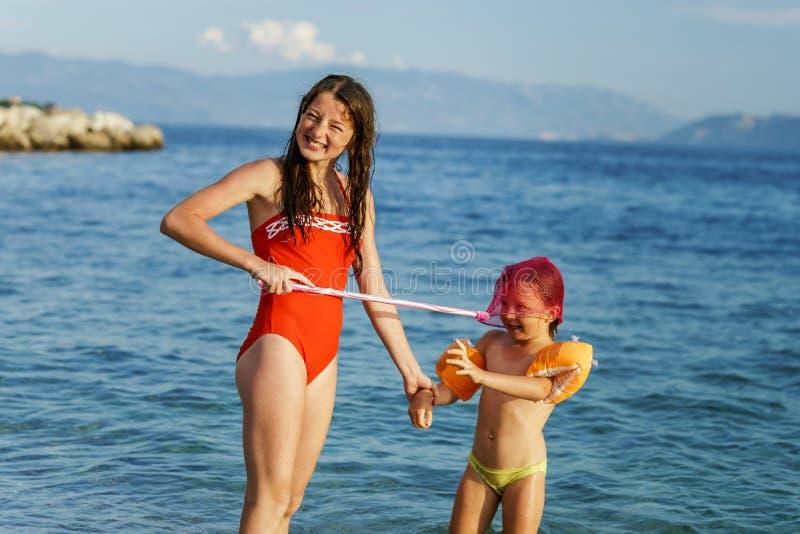 Dos hermanas que juegan a juegos y que nadan en el mar fotos de archivo libres de regalías