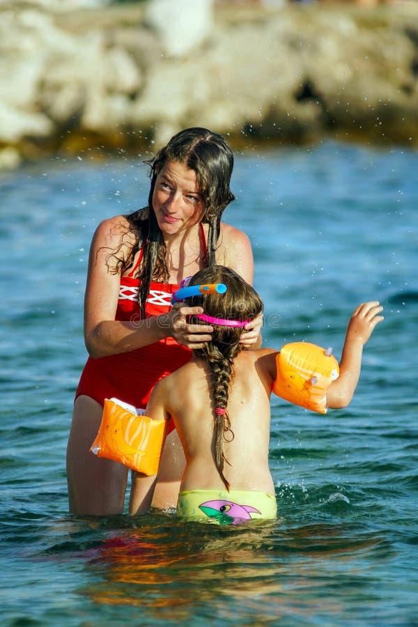 Dos hermanas que juegan a juegos y que nadan en el mar foto de archivo libre de regalías