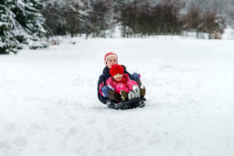Dos hermanas que montan por día de invierno de los trineos foto de archivo