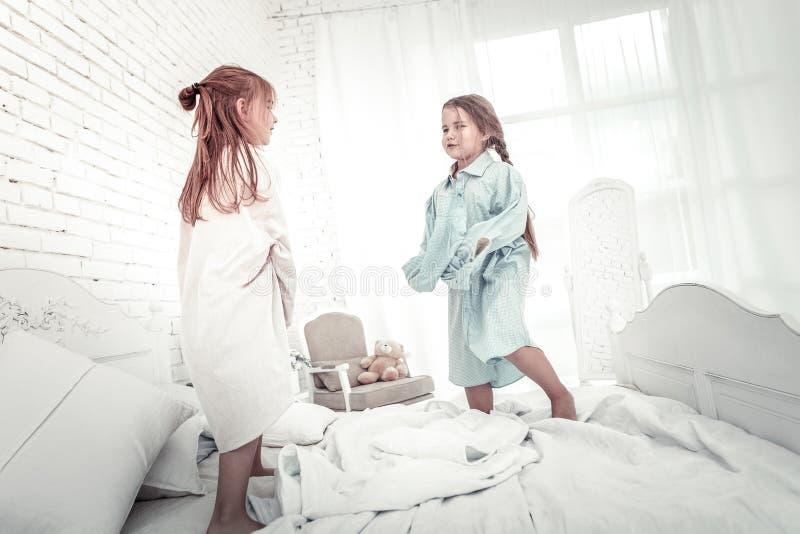 Dos hermanas que saltan en cama en camisas de los padres fotos de archivo