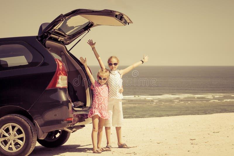 Dos hermanas que se colocan cerca de un coche en la playa fotografía de archivo libre de regalías
