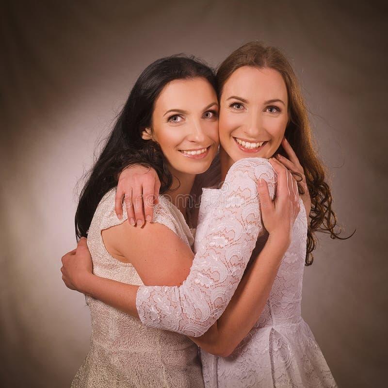 Dos hermanas que sonríen y que abrazan foto de archivo libre de regalías