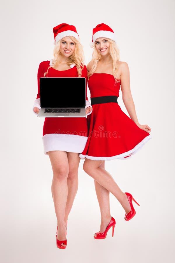 Dos hermanas sonrientes atractivas hermanan sostener el ordenador portátil de la pantalla en blanco imagen de archivo