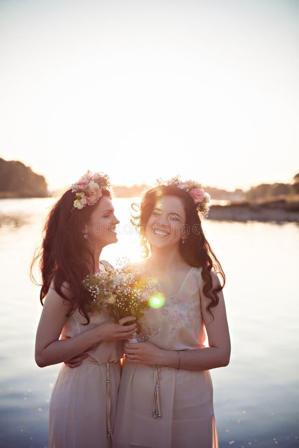 Dos hermanas sonrientes hermosas en los rayos de la puesta del sol imagen de archivo