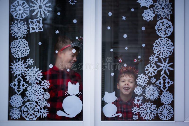 Dos hermanos adorables están mirando a través de la ventana Hay copos de nieve de la decoración del documento sobre la ventana fotos de archivo