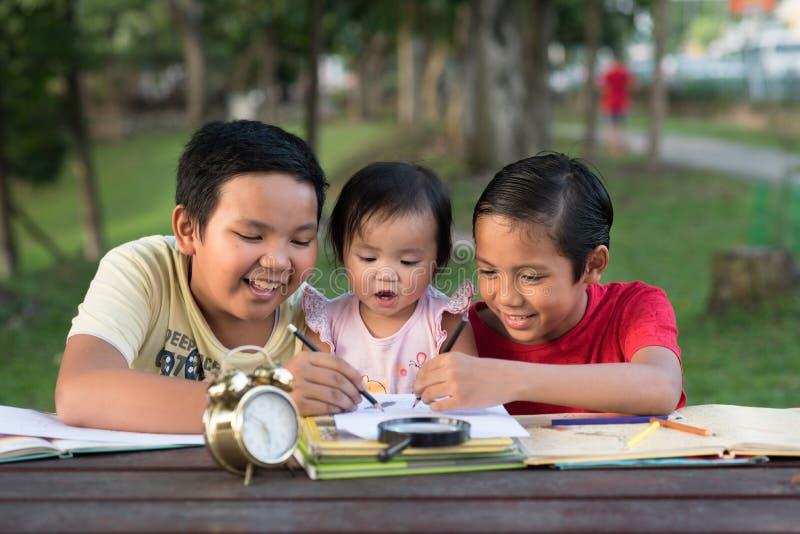 Dos hermanos asiáticos que juegan con su pequeña hermana que une fotos de archivo