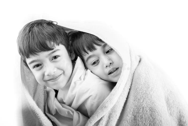 Dos hermanos comparten su blanky en invierno frío foto de archivo