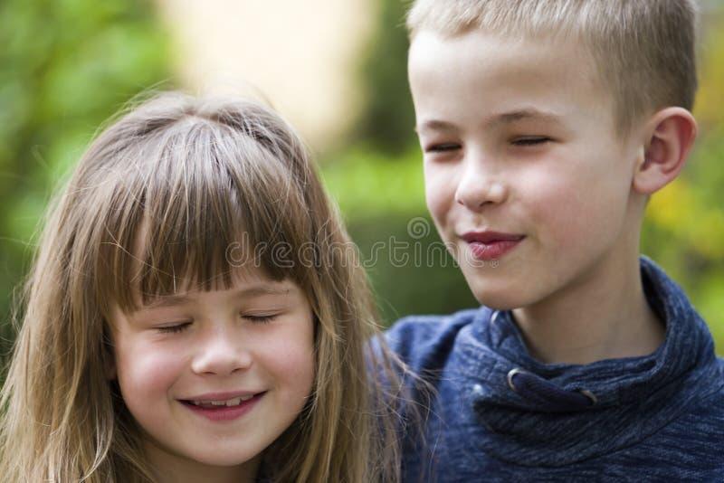 Dos hermanos de pelo rubio lindos de los ni?os, hermano joven del muchacho y aire libre de la muchacha de la hermana en fondo ver fotografía de archivo