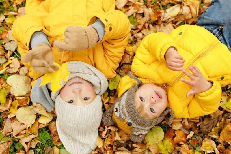 Dos hermanos en hojas de otoño de las chaquetas amarillas mienten encendido imágenes de archivo libres de regalías