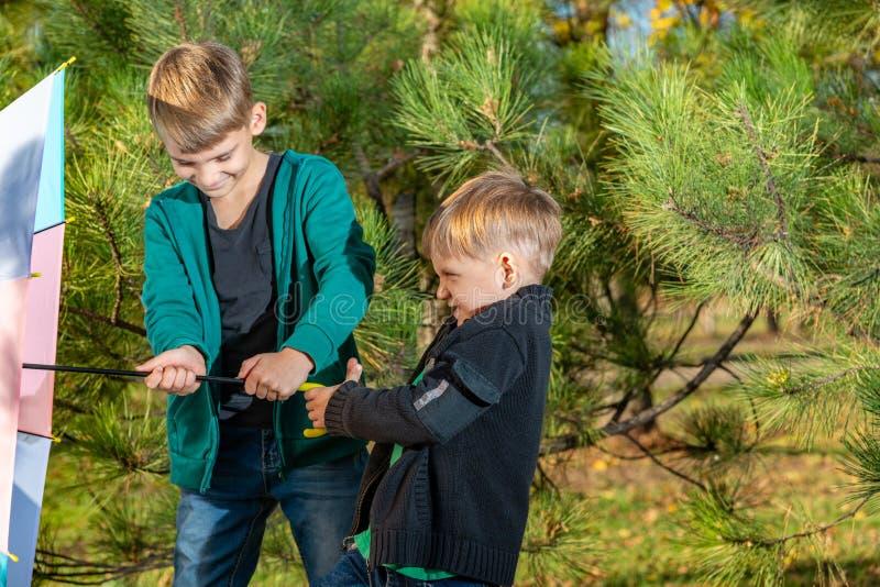 Dos hermanos están tirando de un paraguas coloreado contra el viento en un bosque del pino foto de archivo libre de regalías