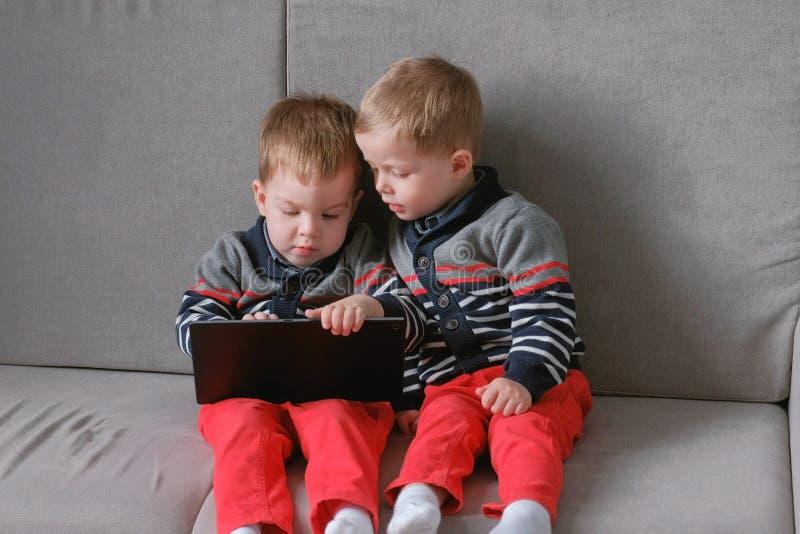 Dos hermanos gemelos se llevan tableta del ` s que se sienta en el sofá Juegos del juego de los niños en la tableta fotografía de archivo