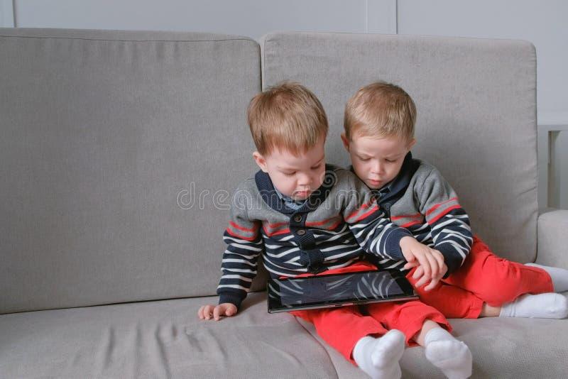 Dos hermanos gemelos se llevan tableta del ` s que se sienta en el sofá Juegos del juego de los niños en la tableta fotos de archivo