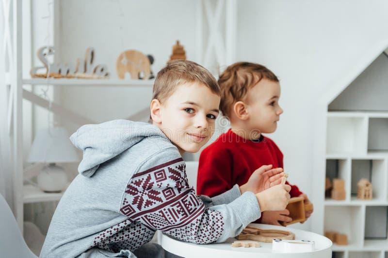 Dos hermanos juegan rompecabezas en la tabla en el cuarto de niños en el estilo escandinavo imagen de archivo