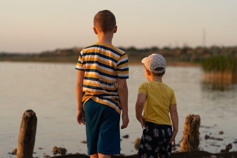 Dos hermanos, muchachos 3 años y 9 años, están mirando la puesta del sol en el lago imagen de archivo libre de regalías
