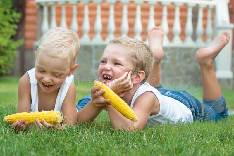 Dos hermanos que mienten en la hierba y comen el maíz en la mazorca en el jardín fotografía de archivo