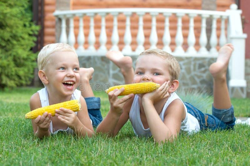 Dos hermanos que mienten en la hierba y comen el maíz en la mazorca en el jardín foto de archivo