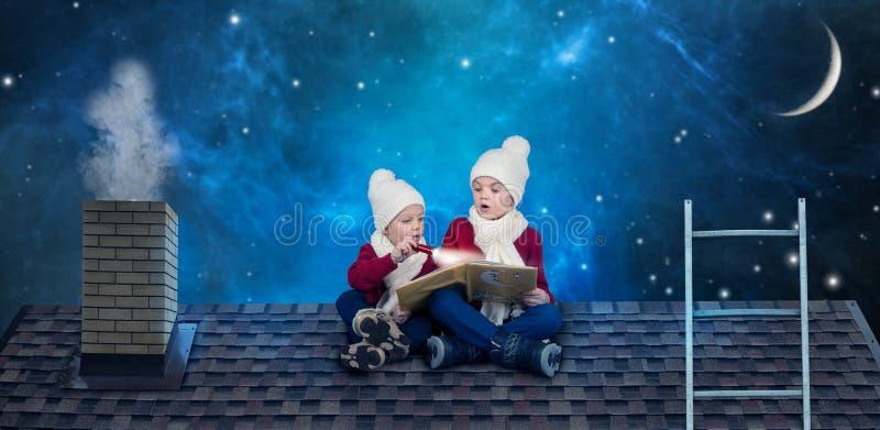 Dos hermanos se sientan el noche de la Navidad en el tejado y leen un libro con cuentos de hadas Antes de milagros de la Navidad foto de archivo libre de regalías