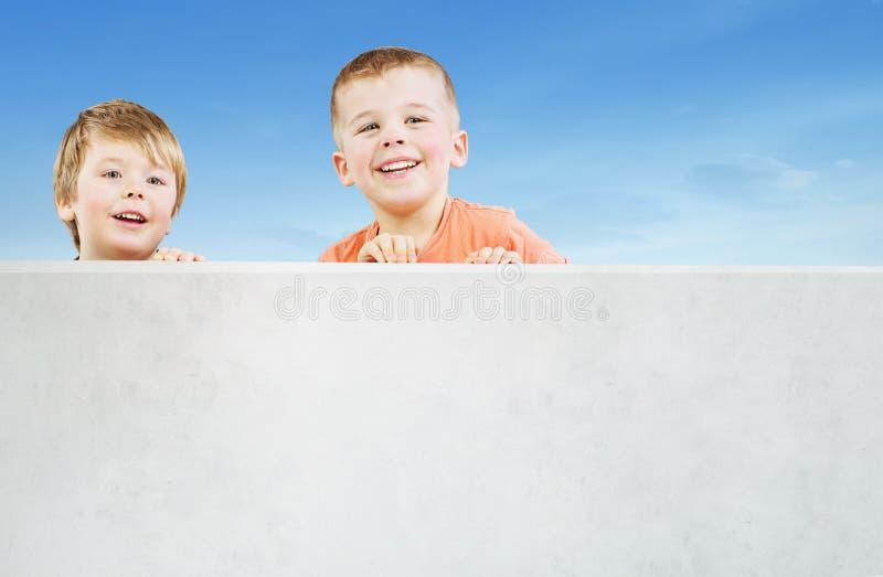 Dos hermanos sonrientes que miran fijamente algo interesante foto de archivo libre de regalías