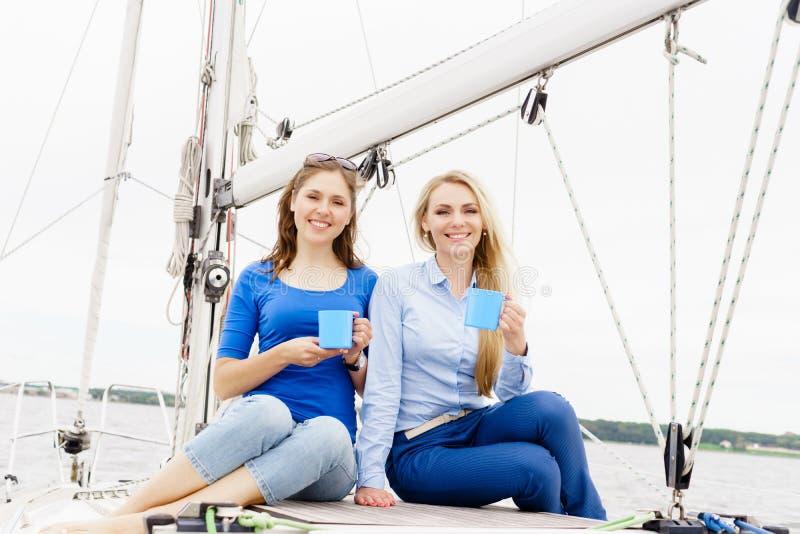Dos hermosos, chicas jóvenes atractivas que beben el café en un yate fotos de archivo