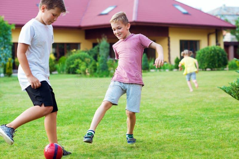 Dos hijos felices que juegan a fútbol con su padre en jardín cerca imagen de archivo