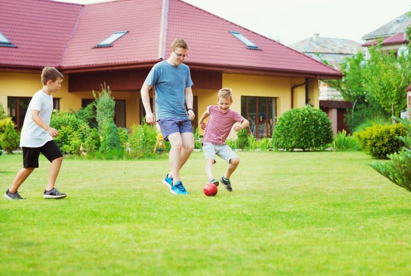 Dos hijos felices que juegan a fútbol con su padre en jardín cerca imágenes de archivo libres de regalías