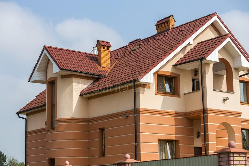 Dos-historias residenciales lujosas costosas modernas grandes cabaña, casa de la familia con el tejado marrón escalonado, altas c imagen de archivo libre de regalías
