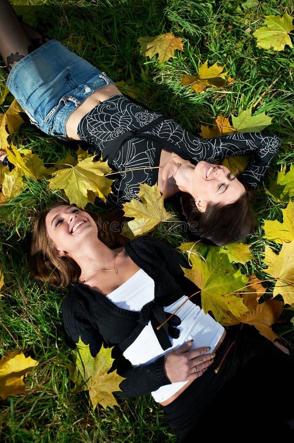 Dos hojas felices de la mujer joven y del amarillo imagen de archivo libre de regalías