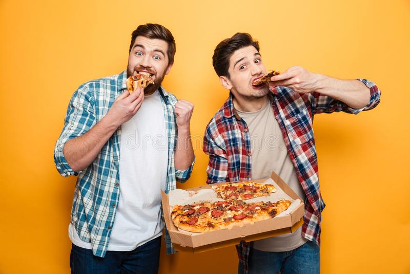 Dos hombres alegres en camisas que comen la pizza imagenes de archivo