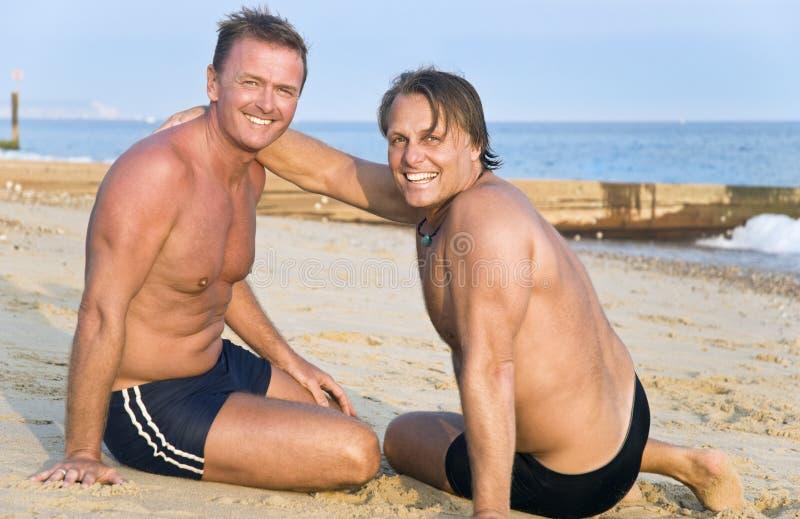 Dos hombres alegres en la playa. imagenes de archivo