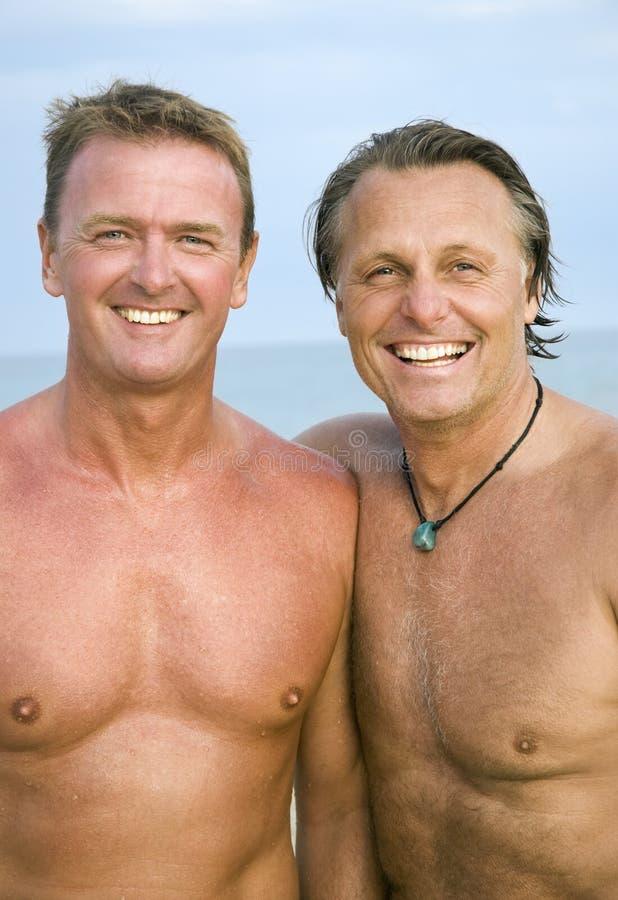Dos hombres alegres en la playa. imagen de archivo libre de regalías