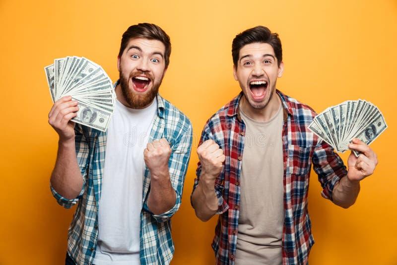 Dos hombres alegres en las camisas que sostienen el dinero y disfrutan imagen de archivo