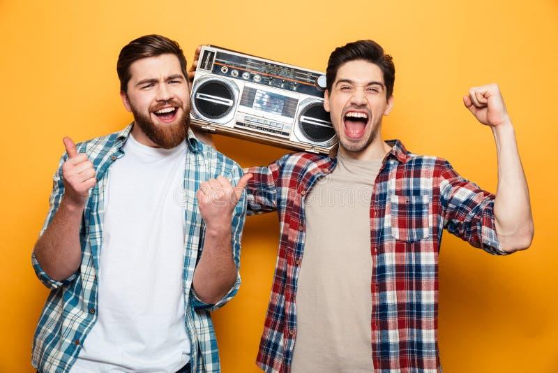 Dos hombres alegres en música que escucha de las camisas del tocadiscos fotografía de archivo