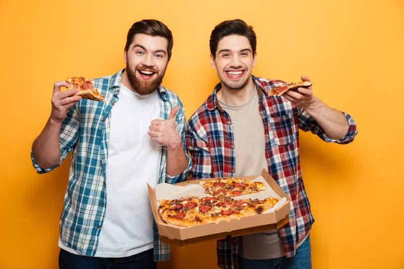 Dos hombres alegres que sostienen la pizza y que miran la cámara imagen de archivo