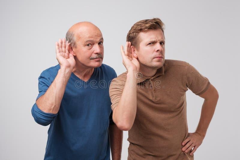 Dos hombres caucásicos que oyen con la mano en el oído aislado en un fondo blanco Hable por favor en alta voz imagen de archivo libre de regalías