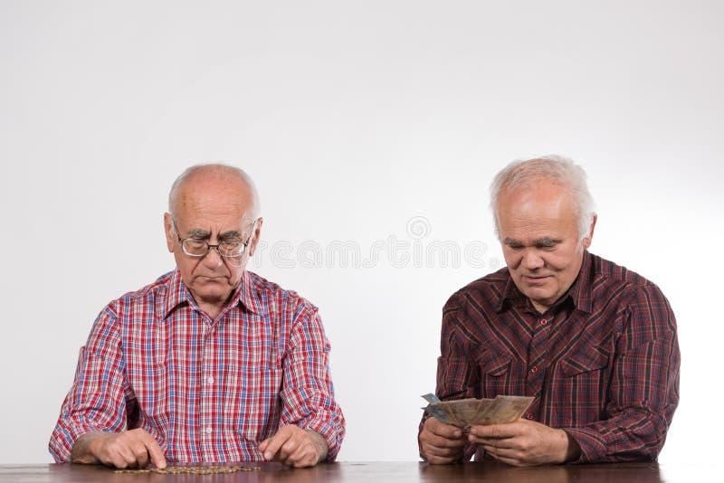 Dos hombres con los billetes y las monedas euro imagenes de archivo
