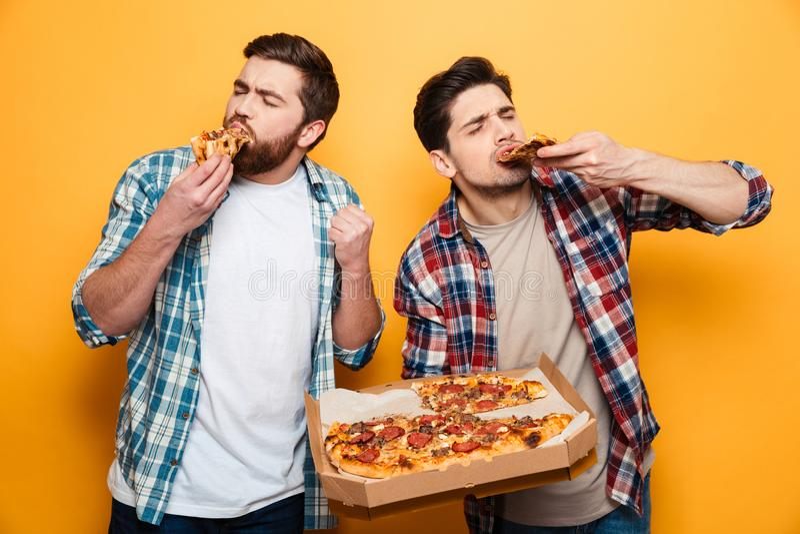 Dos hombres contentos en camisa que comen la pizza fotografía de archivo