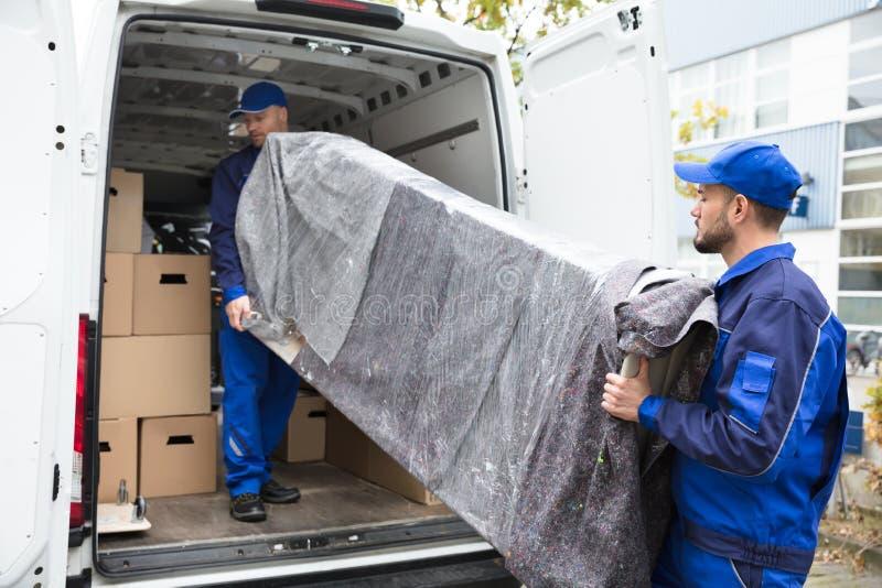 Dos hombres de entrega que descargan los muebles del vehículo foto de archivo