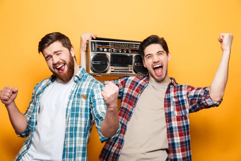 Dos hombres de griterío en las camisas litening música del tocadiscos imagen de archivo