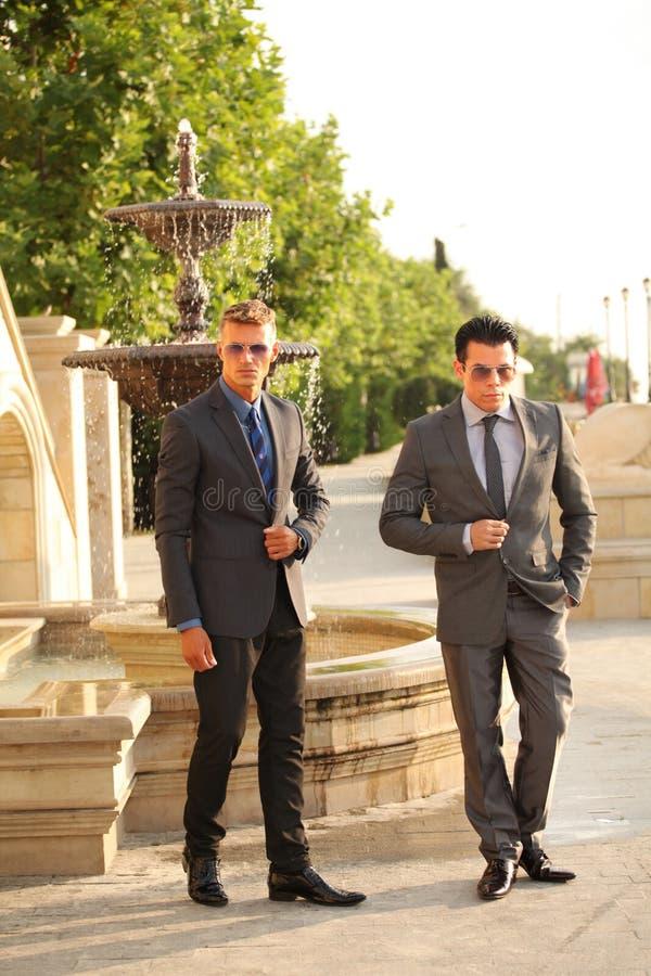 Dos hombres de negocios acercan a la fuente de agua, gafas de sol imágenes de archivo libres de regalías