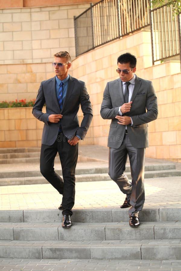 Dos hombres de negocios acercan a las escaleras, gafas de sol imágenes de archivo libres de regalías