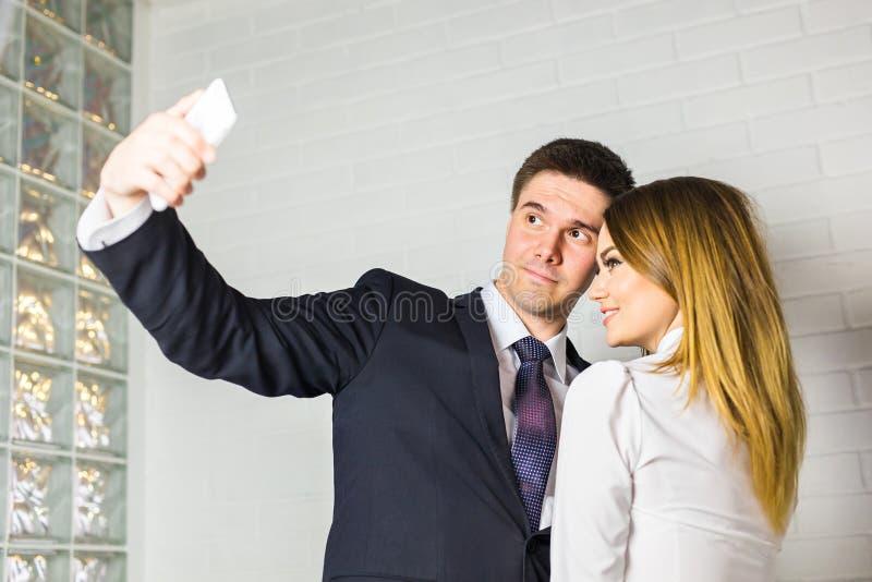 Dos hombres de negocios acertados que toman un Selfie feliz en la oficina foto de archivo libre de regalías