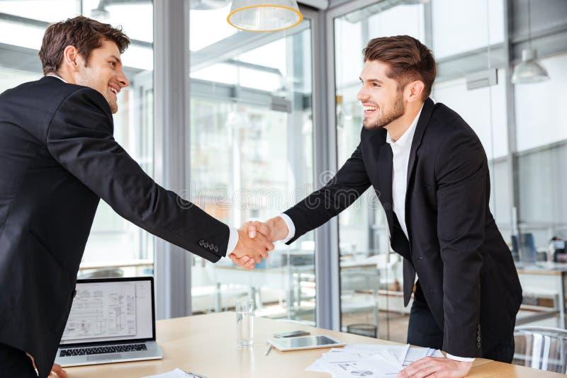 Dos hombres de negocios alegres que sacuden las manos en la reunión de negocios fotografía de archivo libre de regalías