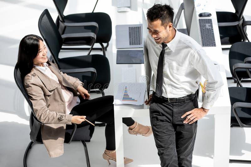 Dos hombres de negocios asiáticos, hombre y mujer tomando con felicidad en el MES imagen de archivo libre de regalías